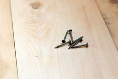 Black screws are on the board, screws for connecting wooden boards.  royalty free stock photo