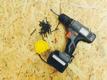 Black screws, a construction tape measure and a wireless drill against the background of the osb.  stock photography