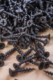 Black screws for fixation of woods on wooden board Royalty Free Stock Photos