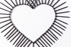 Black screws laid out in the shape of a heart on a white background royalty free stock image