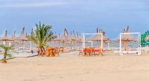 The Black Sea beach, terrace with umbrellas, sand,water and blue sky Stock Photos