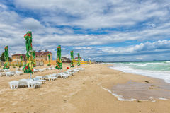 Black Sea beach in a windy day, terrace with umbrellas Stock Photos