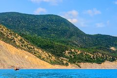Black sea coastline and Caucasus mountains viewed from sea. Scenic coastal sunny landscape with boat sailing off coast stock photography