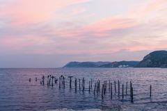Black sea Dawn. Pink clouds, the mountains and birds sitting on metal pipes. Stock Photo