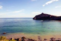 Black Sea med stenar på kusten, himmelblått arkivfoto