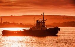 Black Sea port på solnedgången Bogserbåtfartyget är kommande Arkivbild