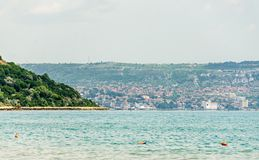 The Black Sea shore, green hills with houses, blue clouds sky Royalty Free Stock Photo