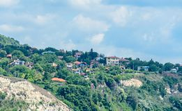 The Black Sea shore, green hills with houses, blue clouds sky. Royalty Free Stock Photography