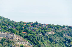 The Black Sea shore, green hills with houses, blue clouds sky. Stock Photography