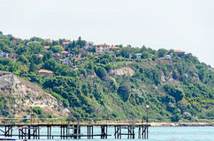 The Black Sea shore, green hills with houses, blue clouds sky. Royalty Free Stock Image