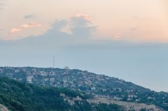 The Black Sea shore, green hills with houses, blue clouds sky. Stock Photo