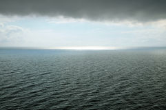 Black sea during a storm. A cloud hangs over water with waves, sunlight away Stock Images