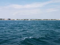 Black sea surface summer wave background. View from yacht. Exotic seascape with clouds and town on horizon. Sea nature tranquility Stock Image
