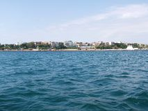 Black sea surface summer wave background. View from yacht. Exotic seascape with clouds and town on horizon. Sea nature tranquility Stock Photos
