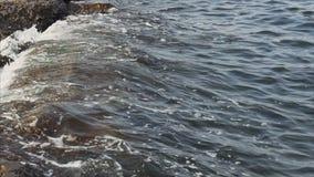 Black Sea waves crash on the stone shore on a summer sunny evening.