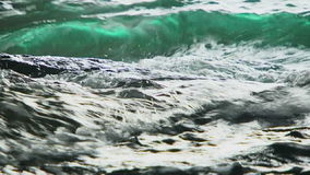 Black Sea Waves Splashing Against Rocks. Close-up video shot in two frames of waves breaking against rocks and splashing around washing the rocks on the stock video footage