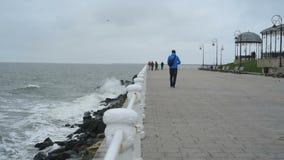 Black sea waves washing the Constanta shore, people walking stock video footage