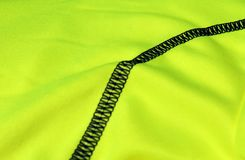 Black seam on a light green textile with folds with focus on the background Royalty Free Stock Images