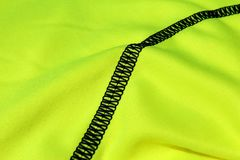 Black seam on a light green textile with folds Royalty Free Stock Images
