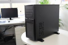 Black server computer in a tower case on a white table in the office, selected focus royalty free stock photo