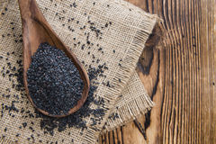 Black Sesame (close-up shot). Small portion of black Sesame (close-up shot) on wooden background royalty free stock photography