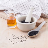 Black sesame oil and sesame seeds Stock Images