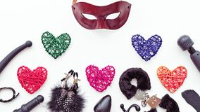 Black sex toys, brown leather venetian mask and colored figures of hearts from rattan are on a light background. Royalty Free Stock Image