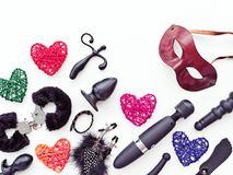 Black sex toys, brown leather venetian mask and colored figures of hearts from rattan are on a light background. Stock Photography
