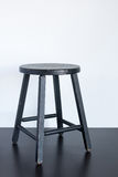 Black shabby stool on wooden surface Stock Photography
