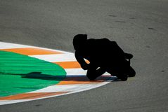 Black motorbike racing pilot tracing curve in circuit royalty free stock images