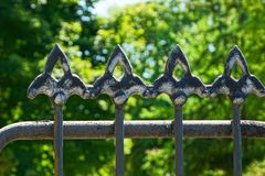 Black sharp steel bars on an old fence against a background of green vegetation. Black sharp steel bars on an old fence against the background of green royalty free stock images