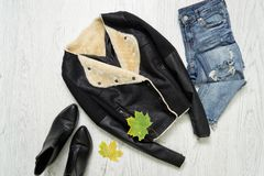 Black sheepskin coat, boots, jeans and maple leaves. Fashionable. Concept Stock Photos