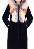 Black sheepskin fur coat with fox collar isolated on grey background. Fur coat on model without face. Outerwear. Cloth. Royalty Free Stock Images