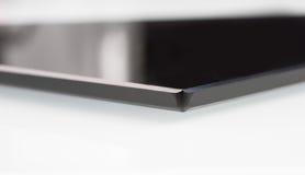 Black sheet glass on a white. closeup Stock Photo