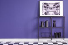 Black shelf with decorations, poster on a purple wall and geomet. Rical floor in creative interior. Place for your furniture royalty free stock photo