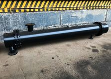 Black shell and tube heat exchanger with concrete wall with yellow and black tape on the background stock photos