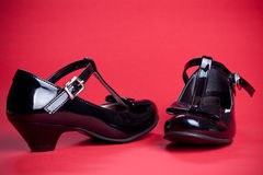 Black shine leather girl shoes with black ribbon on red Royalty Free Stock Images
