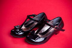 Black shine leather girl shoes with black ribbon on red Royalty Free Stock Photos