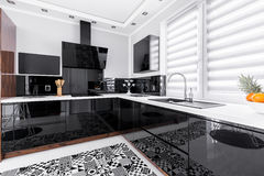Black shining units. In white modern kitchen with patterned rug royalty free stock image