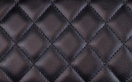 Black quilted leather. Black shiny quilted leather background Stock Image