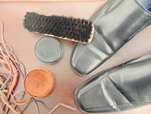 Black shiny shoes with shoe polish, a brush and shoelaces Stock Photos