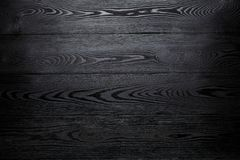 Black shiny wooden abstract background with darkening at the edges stock images