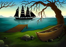 A black ship at the sea across the boat under the tree Royalty Free Stock Photo