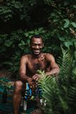 black man sitting in his garden smiling royalty free stock image