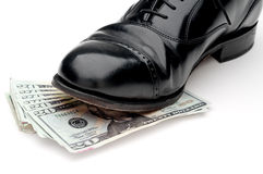 black shoe standing on a pile of money Stock Image