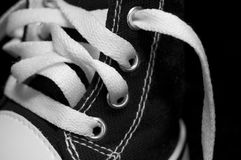 Black Shoe with White Shoelaces. Close-up of a small black shoe with a shallow focus on the bright white shoestrings Stock Photo