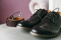 Black shoes and belt on chair. Black shoes and brown belt lie on a chair with a silver cloth Royalty Free Stock Photo