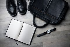 Black shoes briefcase and journal Stock Photos