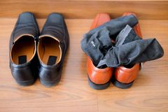Black shoes and brown male shoes with socks. Top view of black shoes and brown male shoes with socks Royalty Free Stock Images