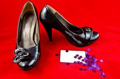 Black shoes and card on red background Stock Images